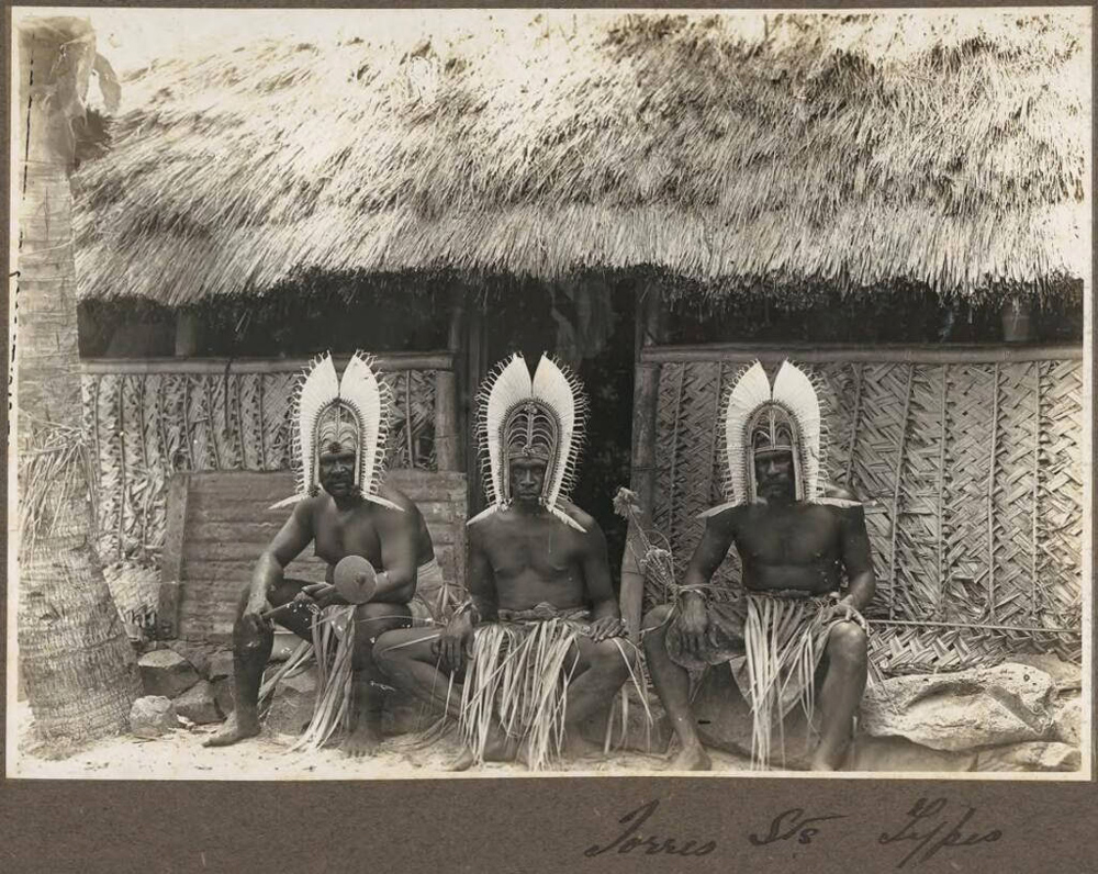 Frank Hurley - Torres Straits Types (three men wearing head dresses sitting outside hut), Torres Strait Islands, circa 1921