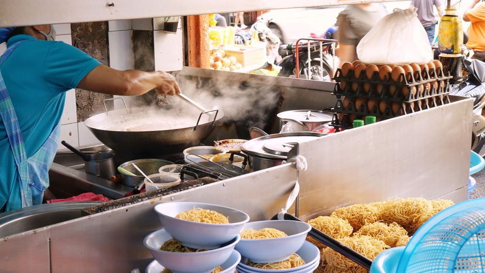 Making Kuay Tiao Rad Na (a stir fried noodle with pork and kale in sticky soup) at shop in Yaowarat, Bangkok, Thailand