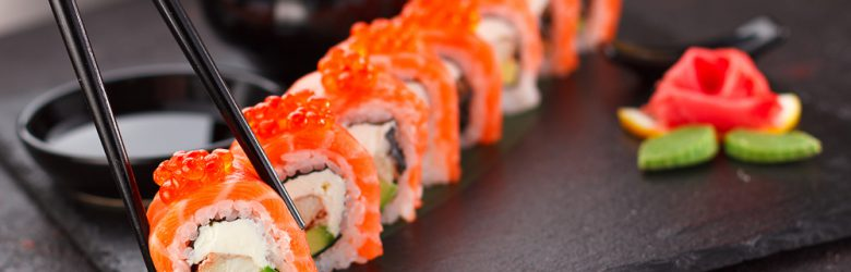 Salmon sushi roll with chopsticks on a stone plate, Japan