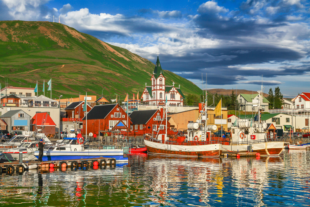 Historic town of Husavik and its harbour at sunset, northern coast of Iceland