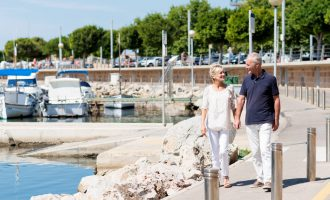 Middle-aged couple walking in marina at a coast in Spain