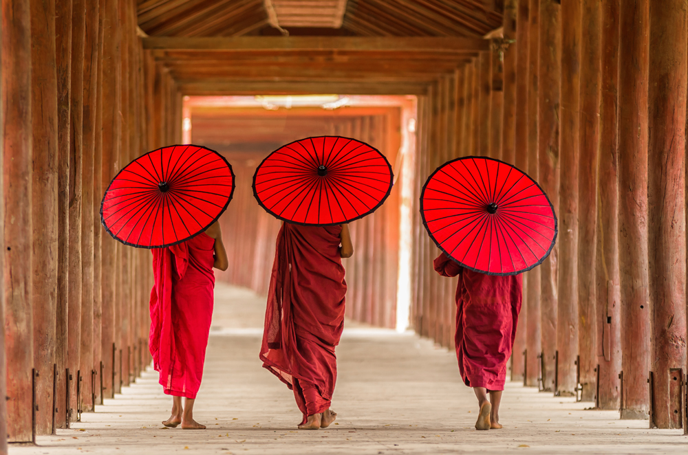 Three Buddhist monks walking in temple, Bagan, Myanmar