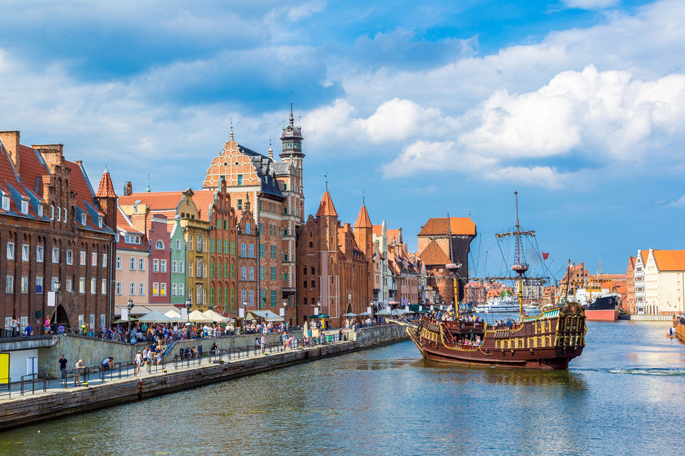 Tourist ship and colourful historic houses reflecting in Motlawa River in port of Gdansk, Poland