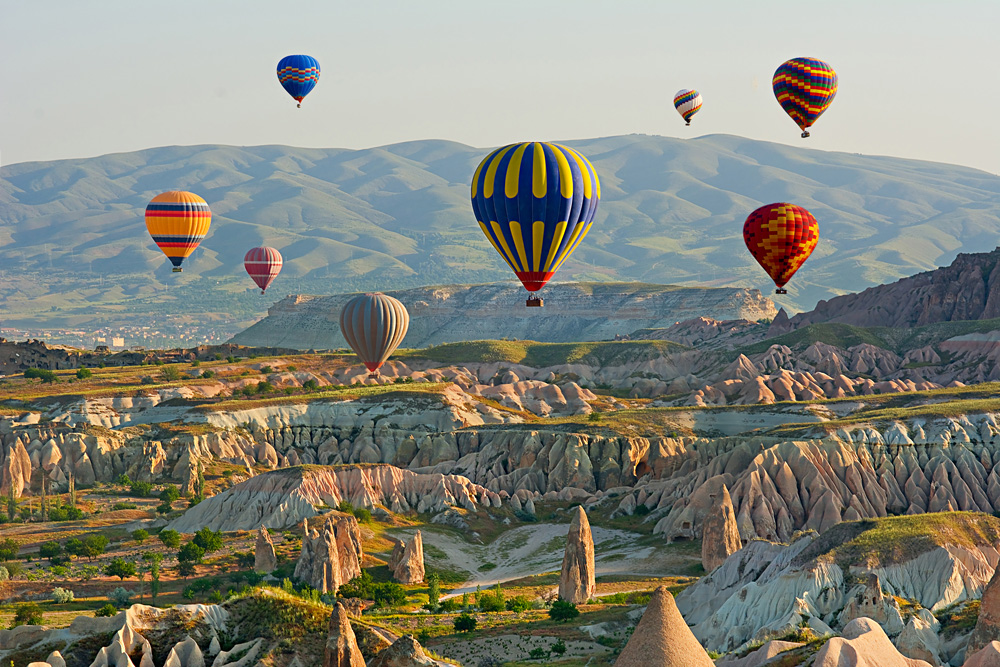 Colourful hot air balloons flying over the valley at Goreme National Park, Cappadocia, Turkey