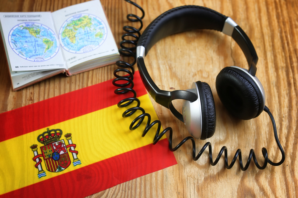 Spanish language course headphone and flag on wooden table