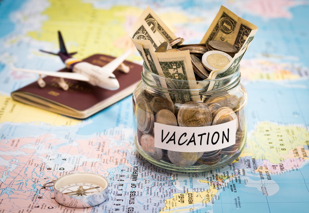 Vacation budget concept with map, small plane, compass, and money jar