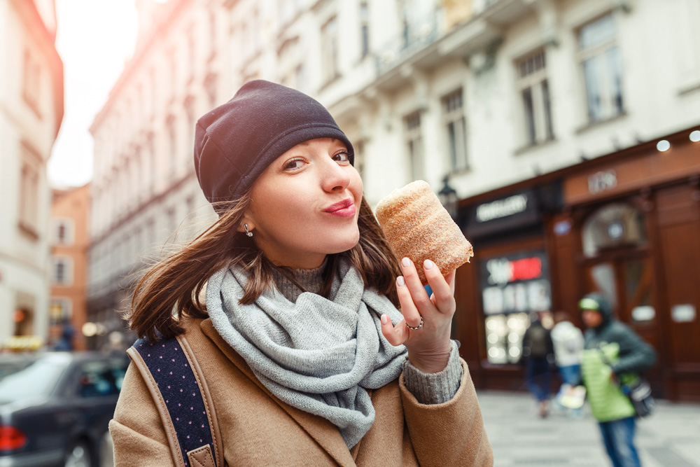 Woman eats trdelnik at a street market in Prague, Czech Republic