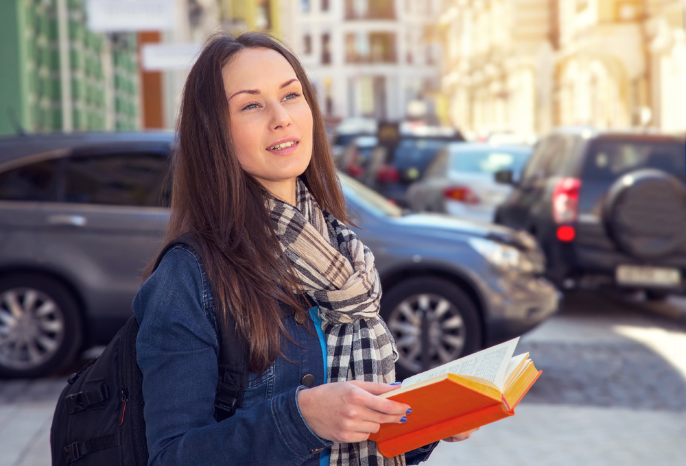 Young female traveller learning foreign languages in a different country