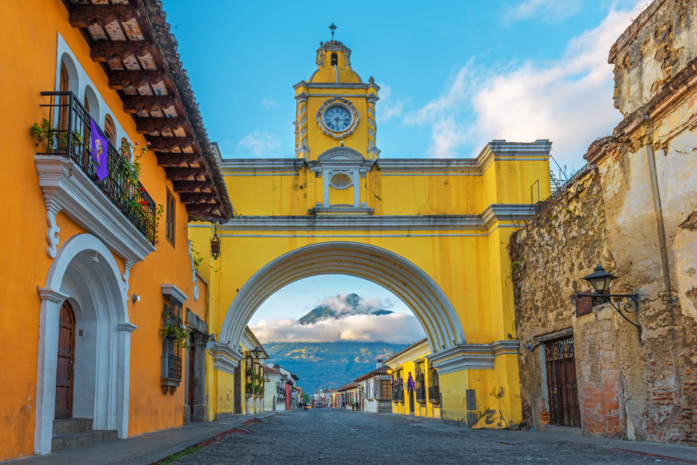 Colourful yellow arch of Guatemala Antigua city at sunrise with the active Agua volcano in the background, Guatemala