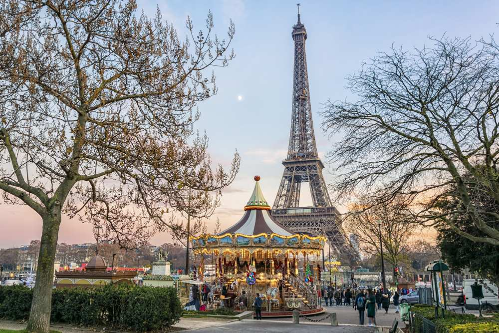 Eiffel Tower and vintage carousel in Paris at sunset in winter, France