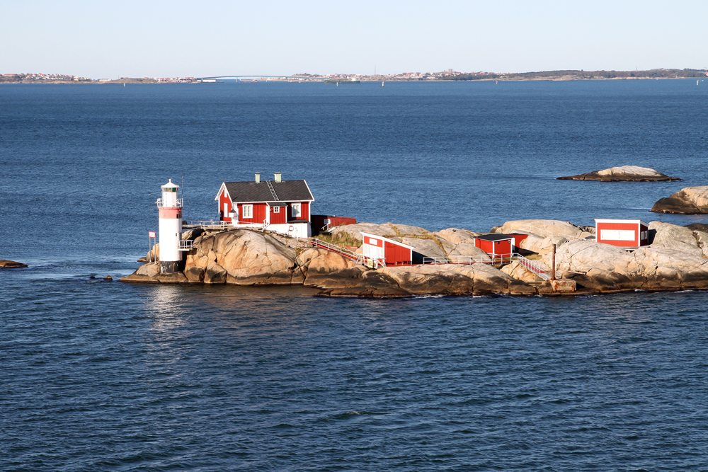 Lighthouse and red buildings on small rocky island in Gothenburg archipelago on the North Sea, Sweden
