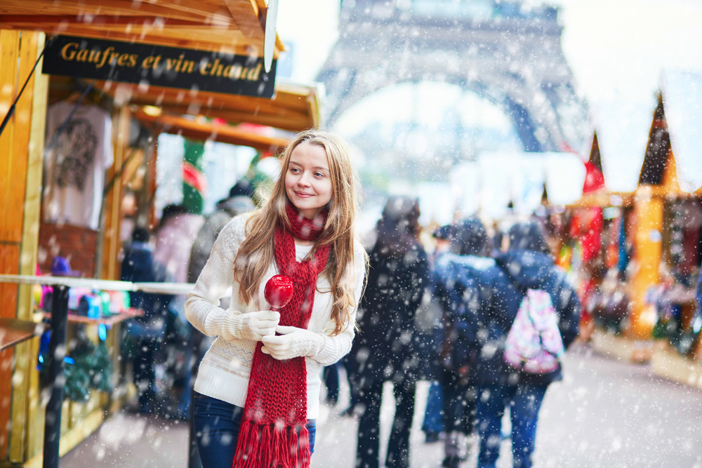 Young girl with caramel apple at a Parisian Christmas market and Eiffel Tower in background at winter, Paris, France