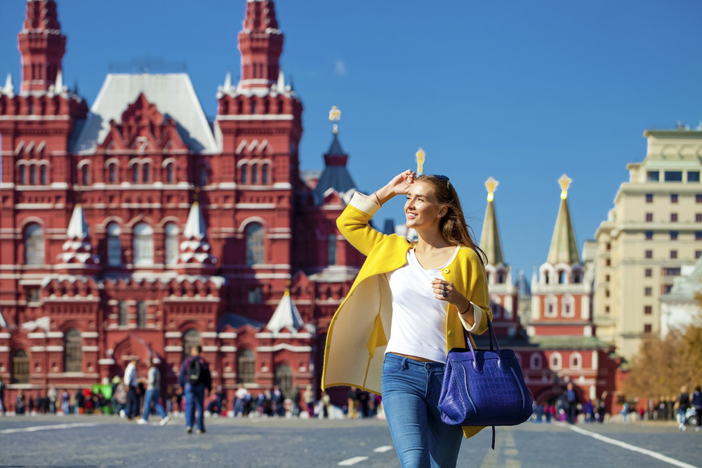 Young happy woman in yellow coat walking in Red Square in Moscow, Russia