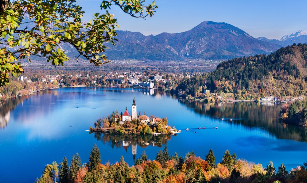 Aerial view of Lake Bled in autumn with Church of the Assumption of Maria and traditional pletna boats, Slovenia