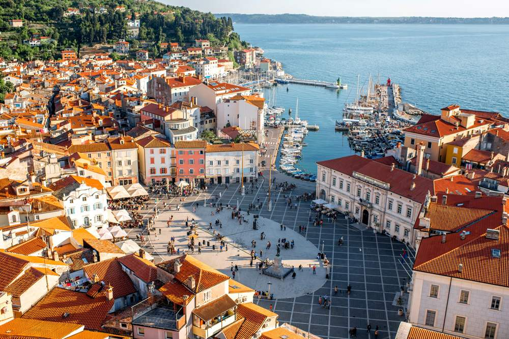 Aerial view of Piran with Tartini Square, ancient buildings with red roofs, and Adriatic Sea, Slovenia