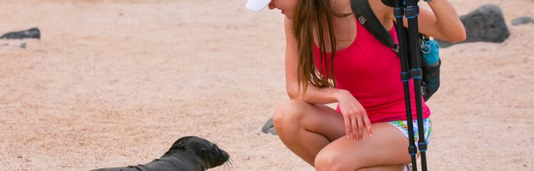 Baby Galapagos sea lion looking at young woman on North Seymour Island, Galapagos National Park, Ecuador