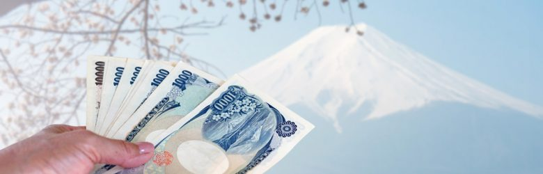 Hand holding Japanese Yen, isolated on blurred Fuji mountain in Japan
