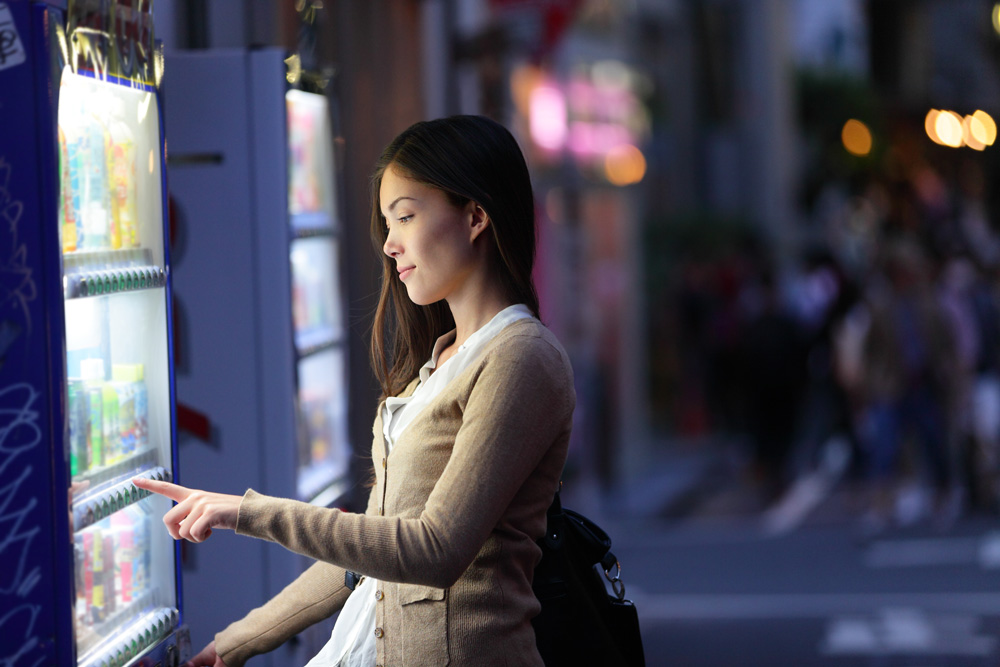 Woman buying drink from vending machine in Tokyo, Japan