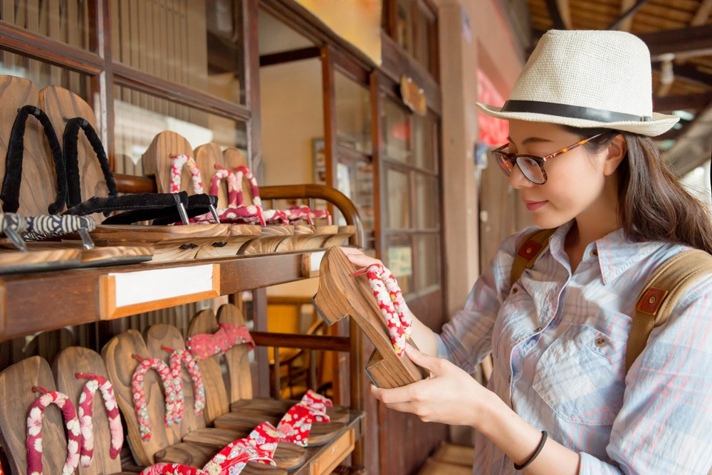 Young female tourist shopping for Japanese komageta shoes on traditional shopping street, Japan