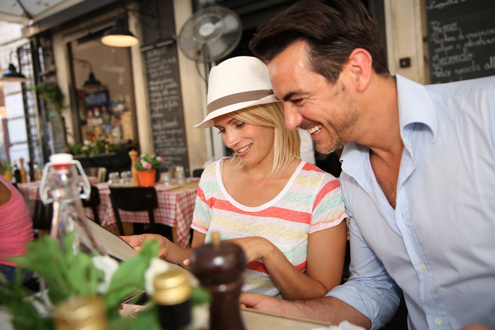 Happy tourist couple sitting at restaurant table in Rome, Italy