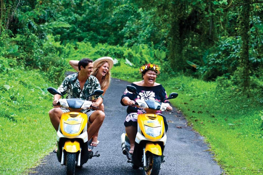 Locals get around scooters in the Cook Islands