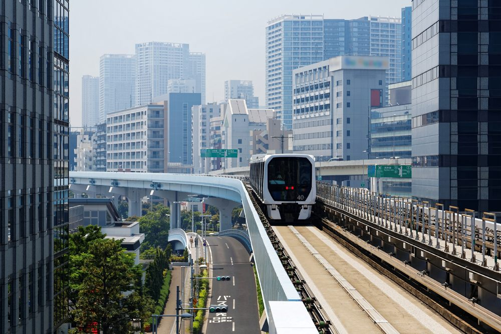 Metro train travelling on elevated rails of Yurikamome Line near Takeshiba Station in downtown Tokyo, Japan