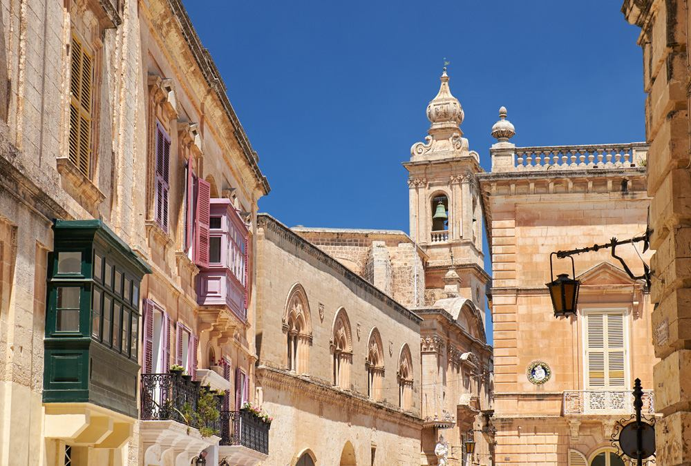 Old Mdina street with traditional Maltese style houses and Carmelite Church Bell Tower in the background, Mdina, Malta