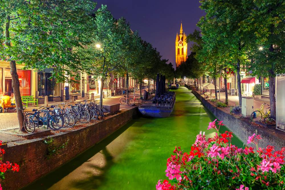 Oude Delft canal and leaning tower of Gothic Protestant Oude Kerk Church at night, Delft, Holland, Netherlands