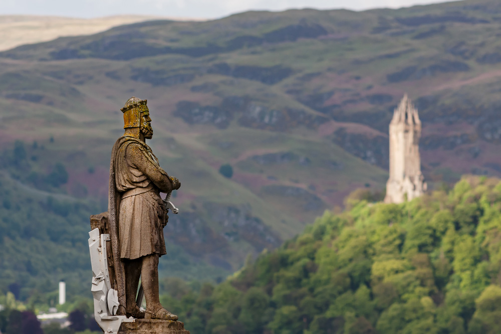 Statue of King Robert I (Robert The Bruce), with National Wallace Monument in background, Stirling, Scotland