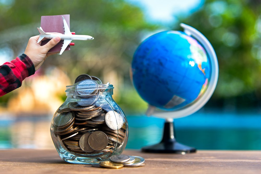 Travel savings in a glass jar with dreams of globetrotting - budget concept