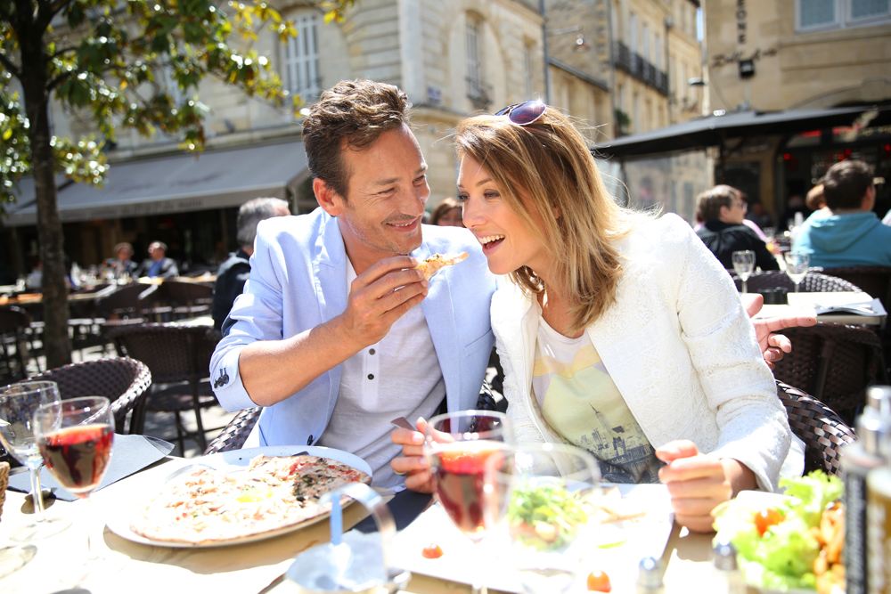 Couple eating lunch at an open restaurant in France