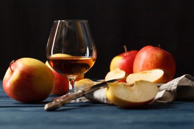 Glass of Calvados (apple brandy) and red apples
