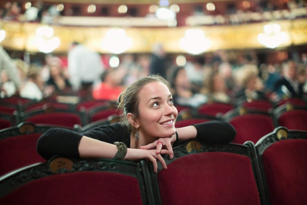 Smiling young woman sitting in auditorium of theatre