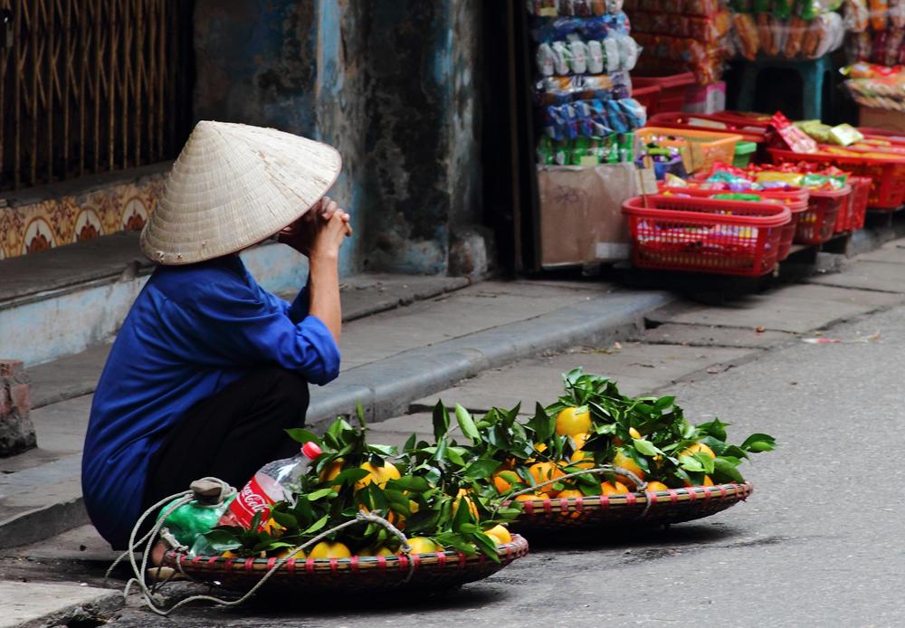 Street vendor in Vietnam selling fruit at a corner in Hanoi, Vietnam cropped