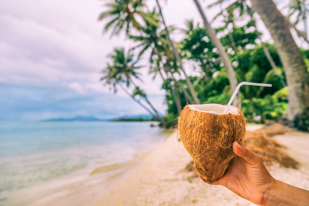 Woman holding fresh coconut water drink on beach in Bora Bora, Tahiti (French Polynesia)