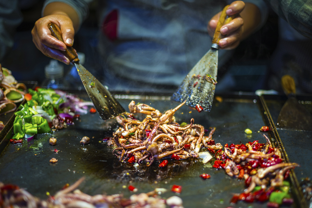 Chef making iron squid in old town of Lijiang, Yunnan Province, China