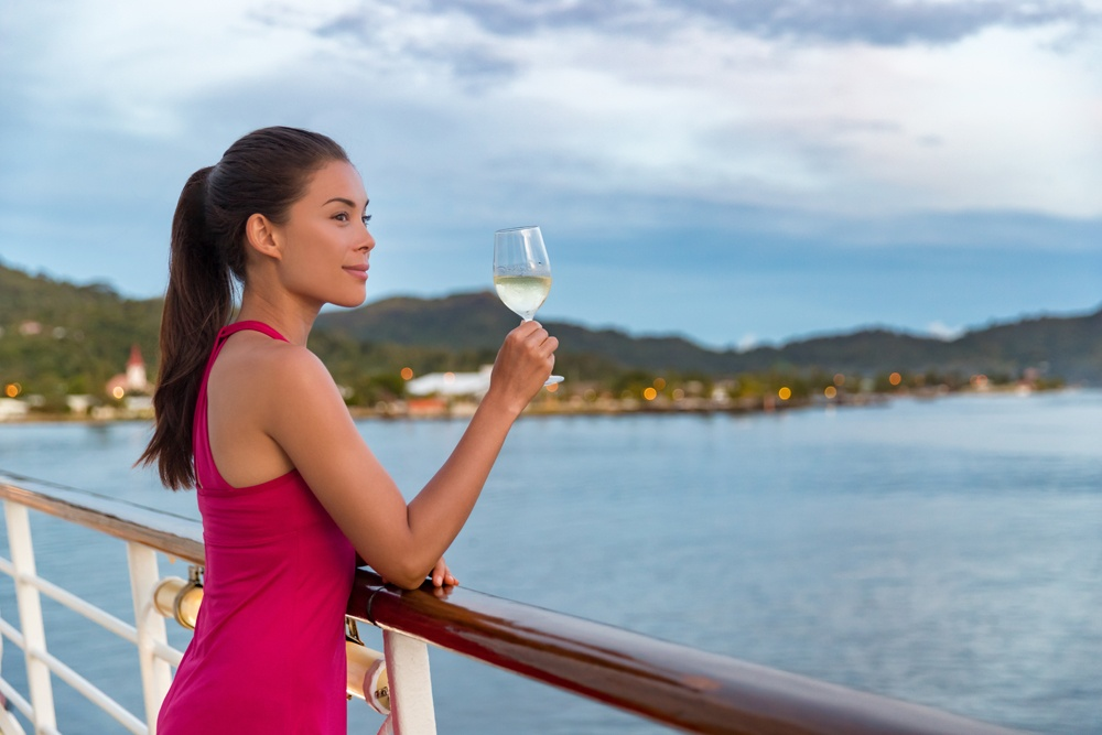 Elegant woman drinking glass of champagne on luxury cruise vacation