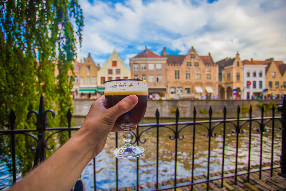 Full glass of beer with Bruges cityscape background, Belgium