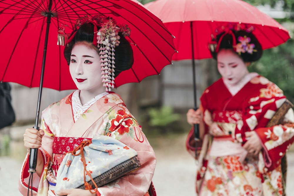 Maiko geisha walking on a street in Gion District, Kyoto, Japan