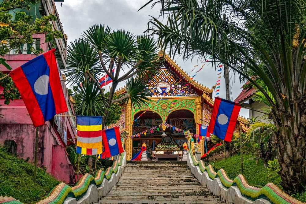 Staircase up hill with view of historic Theravada Buddhist Temple, Huay Xai, Laos