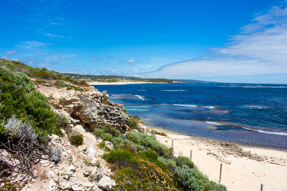 Tide ebbing out from the famous white sandy surfing beach and rocky shore at Margaret River, Western Australia