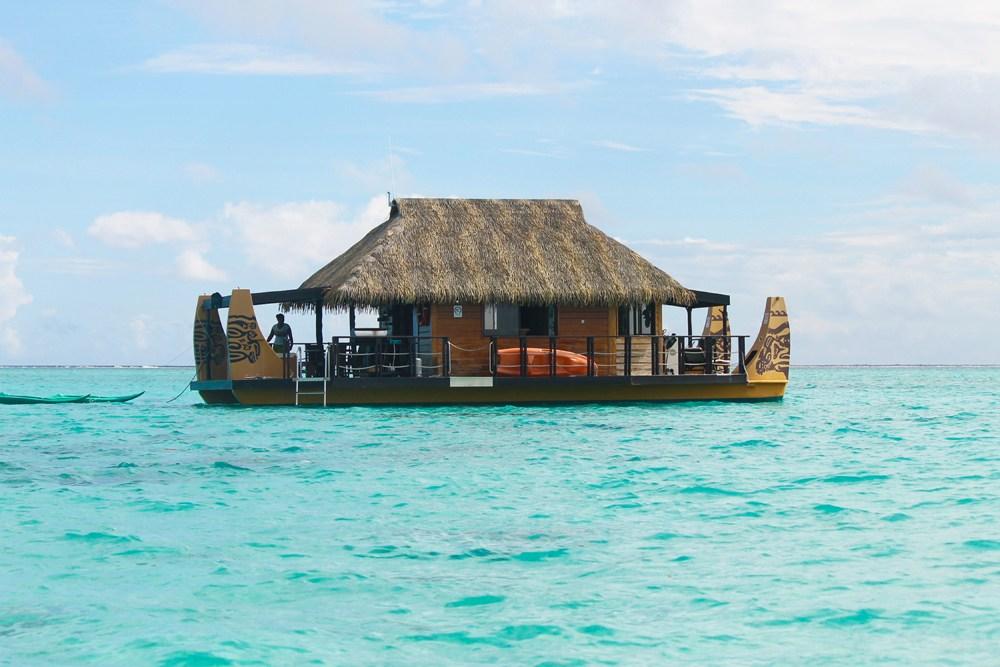 Floating Polynesian boat restaurant on the turquoise sea in Tahaa, Raiatea in Tahiti (French Polynesia)