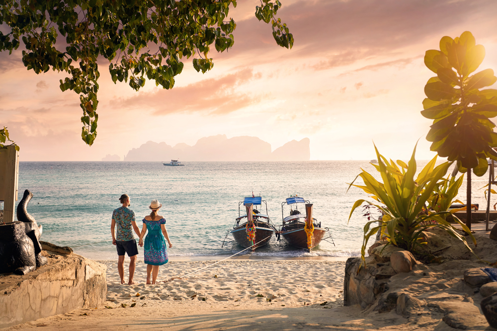 Happy couple on the tropical beach on Phi Phi island at sunset in Southern Thailand