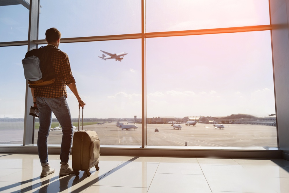 Male tourist at airport watching planes