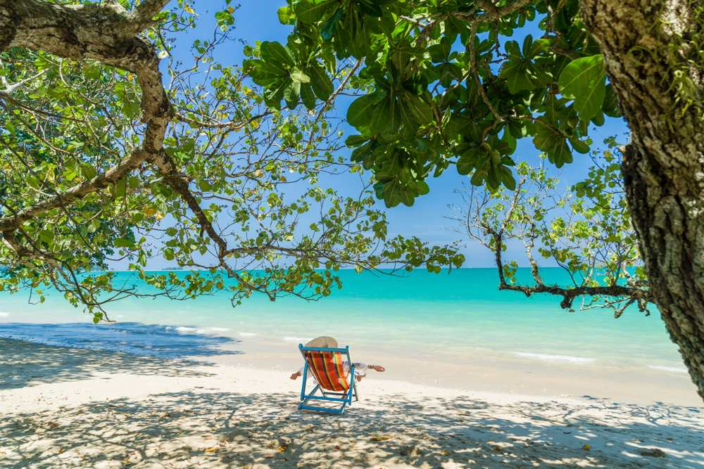 Woman relaxing on white sand beach in Khao Lak, Thailand