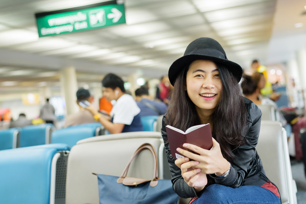 Young Asian woman solo traveller holding passport and waiting for flight travel at airport terminal