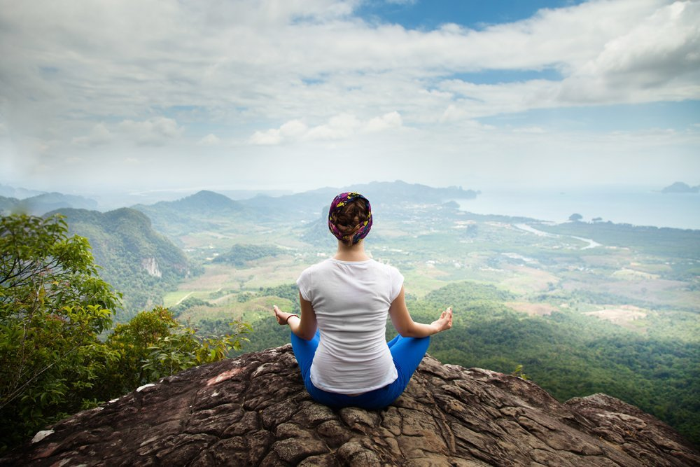 Young woman practicing yoga and meditation in mountains during luxury yoga retreat in Thailand