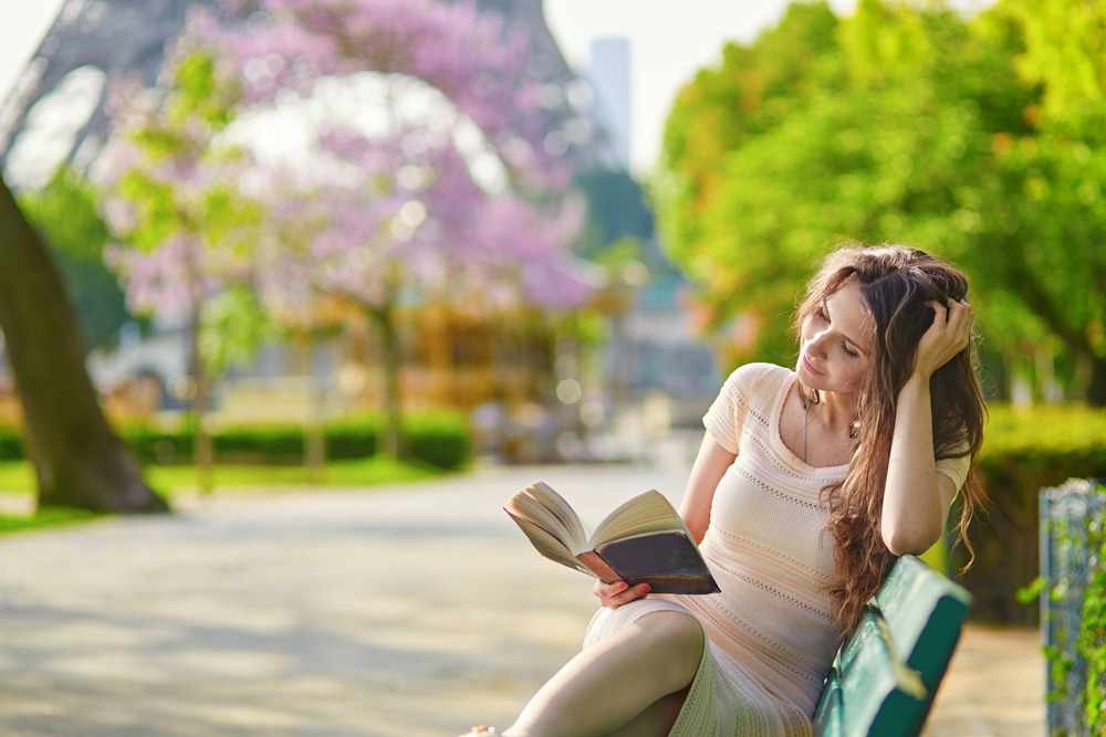 Young woman reading on a bench near the Eiffel Tower in Paris, France