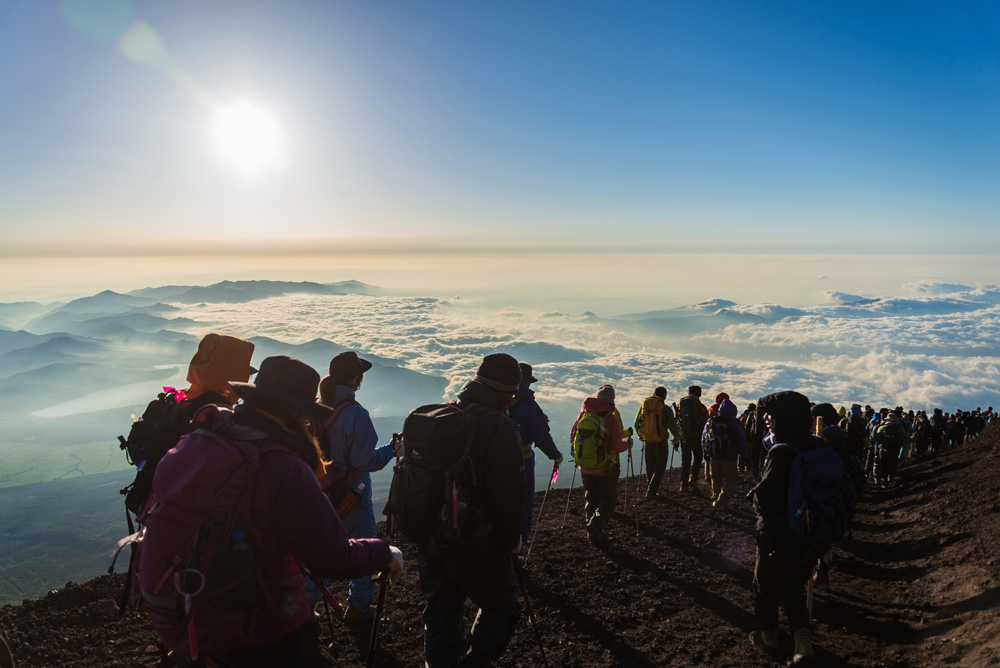Hikers gather during sunrise on the Mount Fuji summit, Japan