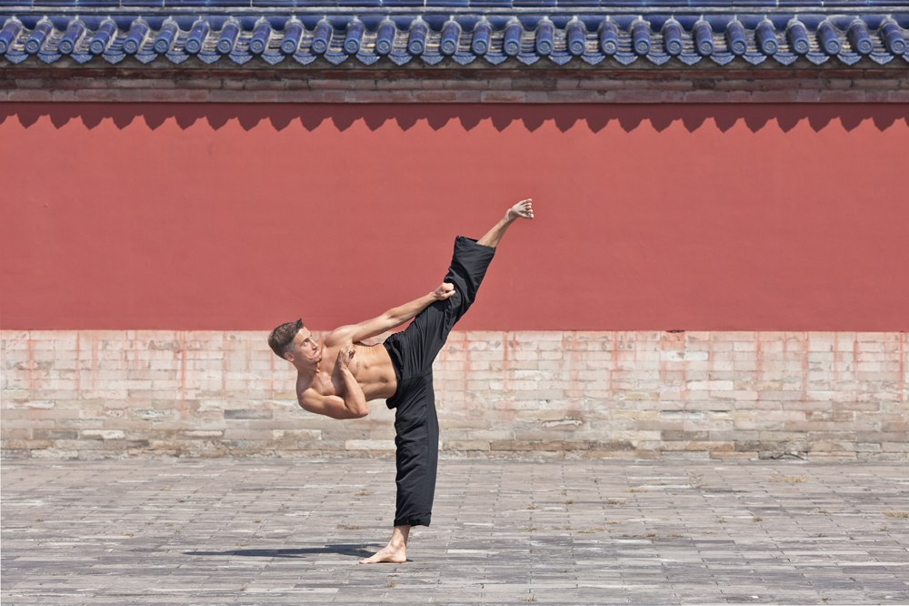 Martial arts master practicing high kick technique at Temple of Heaven, Beijing, China